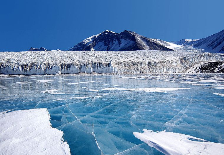 Antarctica: The blue ice covering Lake Fryxell, in the Transantarctic Mountains, comes from glacial meltwater from the Canada Glacier and other smaller glaciers. The freshwater stays on top of the lake and freezes, sealing in briny water below.